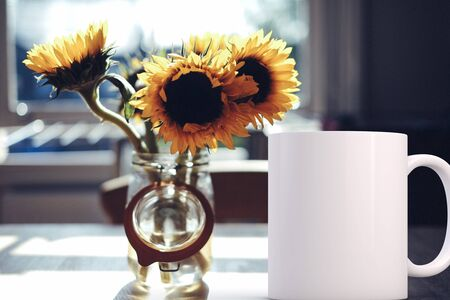 White blank coffee mug mock up, next to a vase of sunflowers, add custom design or quote on to the mug.