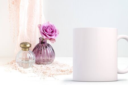 White blank coffee mug mock up, next to a rose in a small glass vase. Add custom design or quote on to coffee mug