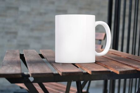 White blank coffee mug mock up on a wooden table outside, add custom design or quote on to mug Stock Photo