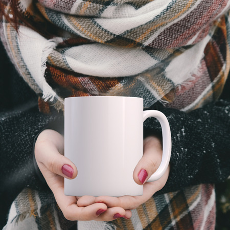 Womans hands holding a white blank coffee mug, Winter theme mock up. Perfect for businesses selling mugs, just overlay your quote or design on to the image. Stock Photo