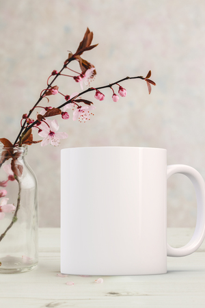 White Mug Mockup - Easter or Spring theme. Blank white mug next to blossom on a tree branch in a glass vase, on a table top. Perfect for businesses selling mugs, just overlay your quote or design on to the image.
