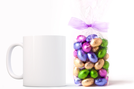 White Mug Mockup - Easter theme. Bag of Easter mini chocolate eggs next to a blank white mug. Perfect for businesses selling mugs, just overlay your quote or design on to the image.  Stock Photo
