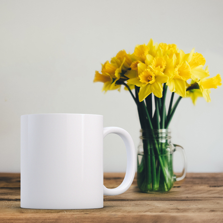 White Mug Mockup - Easter theme. Blank white mug next to a vase of daffodils. Perfect for businesses selling mugs, just overlay your quote or design on to the image.