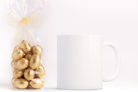 White Mug Mockup - Easter theme. Bag of Easter mini chocolate eggs next to a blank white mug. Perfect for businesses selling mugs, just overlay your quote or design on to the image.
