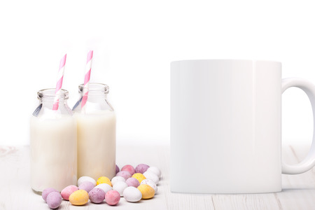 Two mini milk bottles with straws and chocolate mini eggs scattered around the milk bottles.