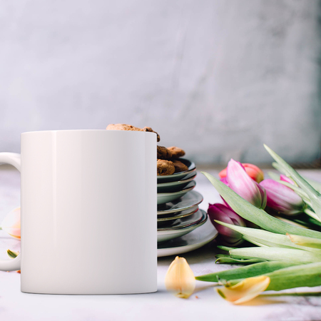 White Mug Mockup - Easter theme. Blank mug infront of a plate of ccokies with a bunch of tulips on a table top. Perfect for businesses selling mugs, just overlay your quote or design on to the image.