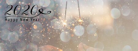 New Year banner, header for social media. Scales down to fit a social media header size. Sparklers against a background with bokeh and falling snow effect. Happy New Year 2020 quote.