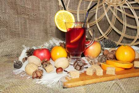 Mulled wine with spices and fruit on wooden background. Side view. Фото со стока