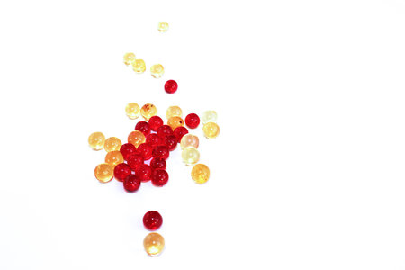 Vitamins. Red and yellow transparent capsules with a white background.