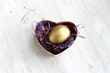 The Golden Egg in Gift Box on White Wooden Background. Easter theme
