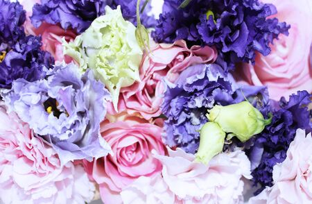 Festive floral arrangement in pastel colors. Purple and pink flowers on white background. Irises, roses and carnations in a chic bouquet. Background for greetings, invitations, cards for wedding