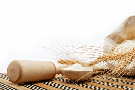Flour and wheat grain with wooden spoon on a wooden table