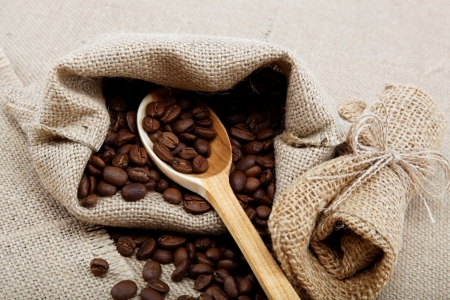 Coffee beans in a spoon on sacking  photo