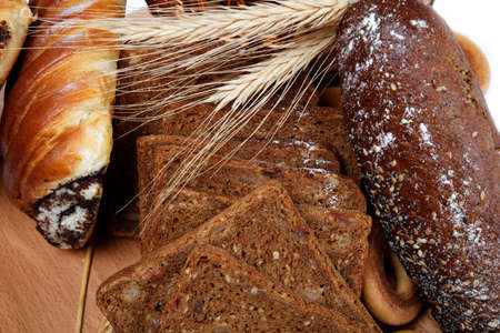 large variety of bread, still life isolate on a wooden table over white. photo