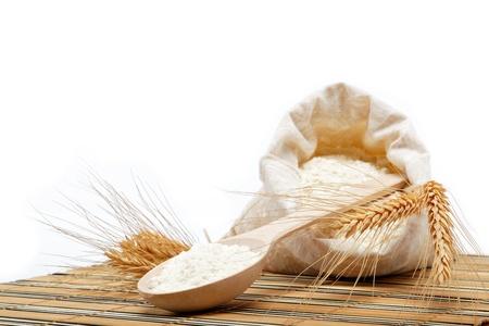 harina: Harina de trigo y de cereales con cuchara de madera sobre una mesa de madera.