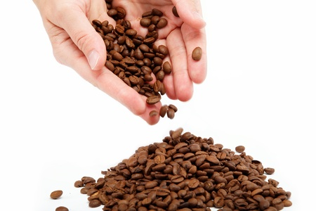 Beautiful womans hand holding the coffee beans, isolated on white. photo
