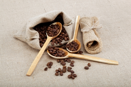 Coffee beans in a spoons on sacking. photo