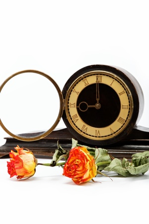timekeeper: Dry roses and antique wooden table clockon a white background. Stock Photo