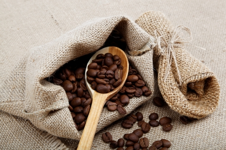 Coffee beans in a spoon on sacking. photo