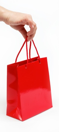 Red gift bag in the women's hand on a white background. photo