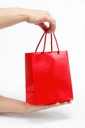 Red gift bag in the womens hands on a white background. photo