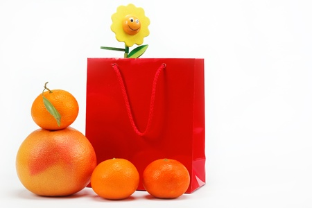 Red Gift Bag and citrus fruits on a white background. photo