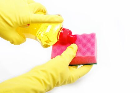 Hands in rubber gloves with a bottle of detergent and sponge on a white background. The detergent is poured on a sponge. photo
