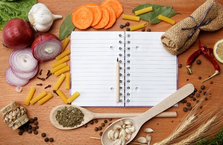 notebook for recipes and spices on wooden table Standard-Bild