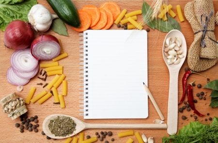 food table: notebook for recipes and spices on wooden table Stock Photo