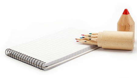Colored pencils in a wooden case and a notebook on white. photo