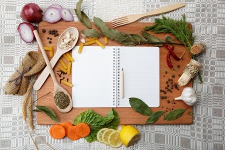 vegetable cook: notebook per ricette e spezie sul tavolo in legno Archivio Fotografico