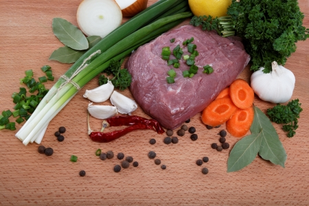 raw meat, vegetables and spices isolated on a wooden table. photo