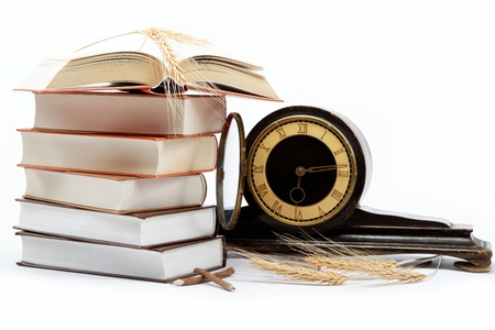A stack of books and antique clock on a white background. photo