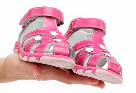 women's hand: Pink Childrens sandals in the womens hand isolated on white. Stock Photo