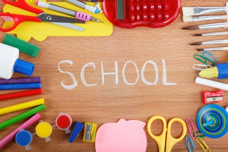 utiles escolares: oficina y accesorios de los estudiantes en fondo de madera Volver al concepto de escuela