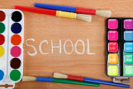 Paint and brushes on a wooden table  Back to school concept  photo