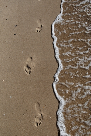 Footprints in the sand by the sea Stock Photo