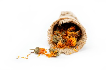 Herbs. Dried calendula or pot marigold flowers in a linen package isolated on white background. Stock Photo - 15584140