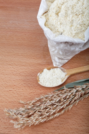 Corn flour in a bag with wooden spoon and ear on wooden table   photo