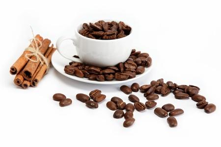 granos de cafe: taza con granos de caf� aislados en el fondo blanco