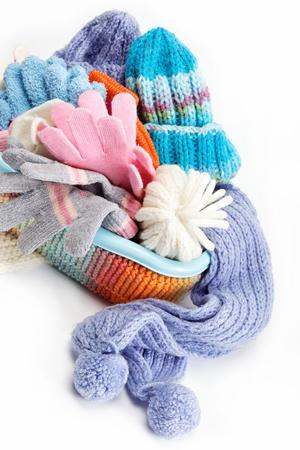 冬季附件集合。帽子,圍巾和手套在容器中,被隔絕在白色背景。 版權商用圖片