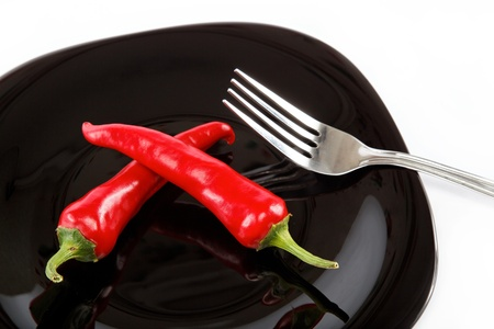 Red hot chili peppers in a black plate with a fork, isolated on white background. photo