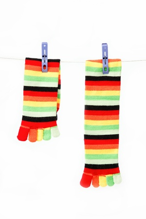 Colorful fun socks attached clothespin hanging from a rope. photo