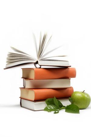 Una pila de libros y la manzana verde sobre un fondo blanco