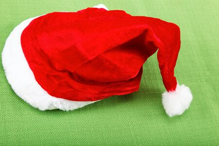 pompon: Santa Claus hat on the green cloth. Stock Photo
