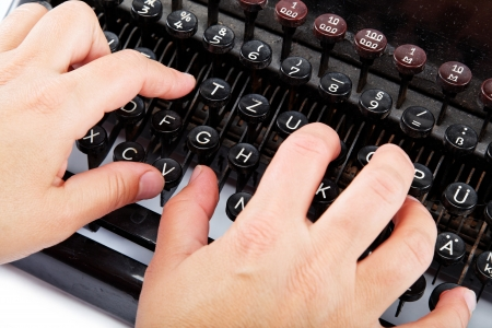 Female hands typing on the keyboard of the old mechanical typewriter. photo