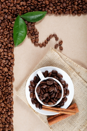 Cup with coffee beans and cinnamon sticks on sackcloth. photo
