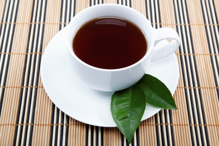 A cup of black tea with a saucer on a wooden table. Stock Photo - 16910507