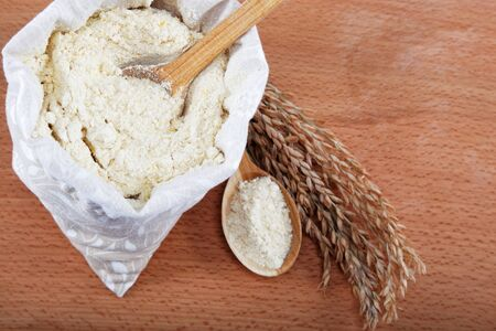 Corn flour in a bag with wooden spoon and ear on wooden table. photo