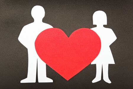 Silhouettes of men, women and heart cut out of paper on a black background. Happy couple in love. photo